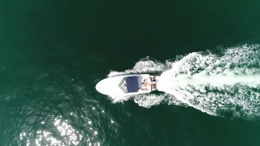 Aerial top down view of motorboat with people sun tanning on stern side deck of boat also known as speedboat or powerboat is vessel which is powered by an engine beautiful summer day 4k quality
