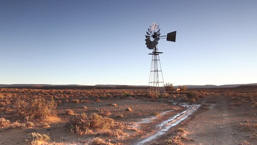 Windpump windmill barelying turning slowly on a calm day pan over to Karoo Desert of South Africa