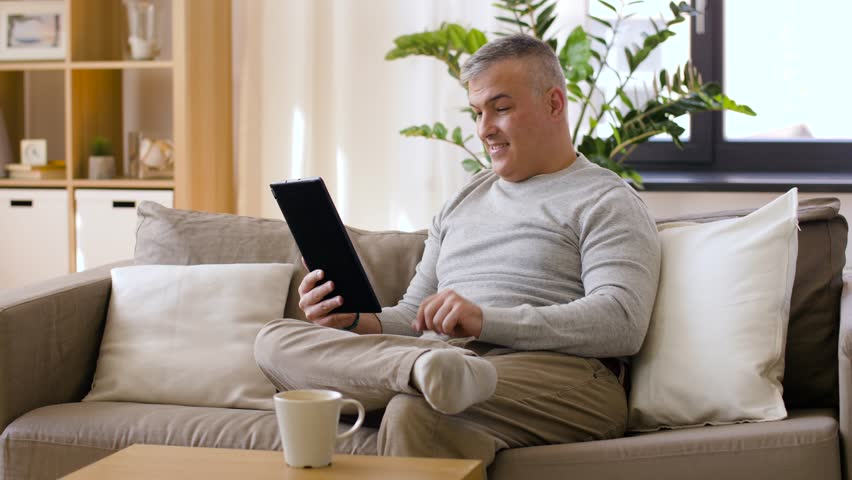 Technology, people and communication concept - happy man with tablet pc computer having video chat at home | Shutterstock HD Video #1011411395