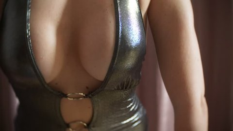 a hot seductive model in a mini-dress dancing an erotic private dance . slim body and big tits. 4k
