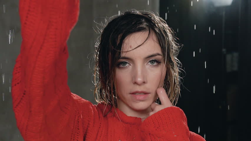 Close up of a girl in red sweater who looks at the camera she has a wet hair from the water rain. The wet girl under the drops of water looks into the camera. Studio shooting. Portrait, slow motion