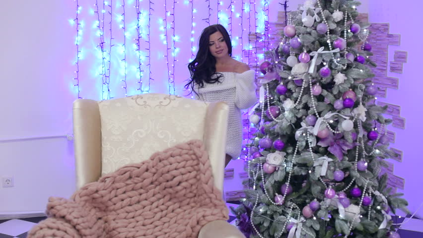 Sexy half-naked girl leaned on a white soft chair at home on the background of a Christmas tree and flashing purple lights. | Shutterstock HD Video #1011453635