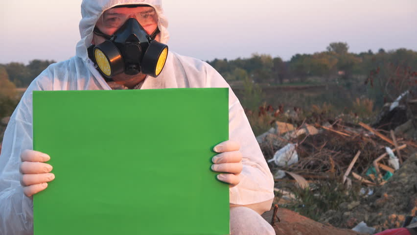 Scientist with protective mask and white suit  hold green screen   Shutterstock HD Video #1011467075