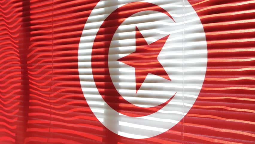Tunisian flag hanging at wide jalousie window. Closeup  #1011468845