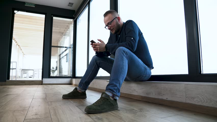 Depressed young man sits near panoramic window and writes something on his mobile phone.  | Shutterstock HD Video #1011481535
