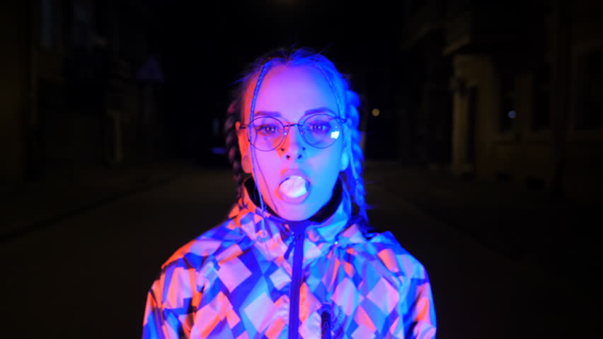 Attractive pretty girl with unusual hairstyle walking on street with light at night. Dyed blue hair in braids. Pensive hipster teenager in glasses chews cud and blows bubbles