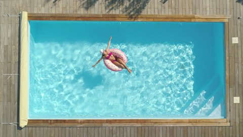 AERIAL, TOP DOWN, CINEMAGRAPH: Cheerful young woman sunbathing while relaxing on a cool inflatable doughnut in her backyard pool. Happy girl in pink bikini lying on a funny floatie in amazing pool.