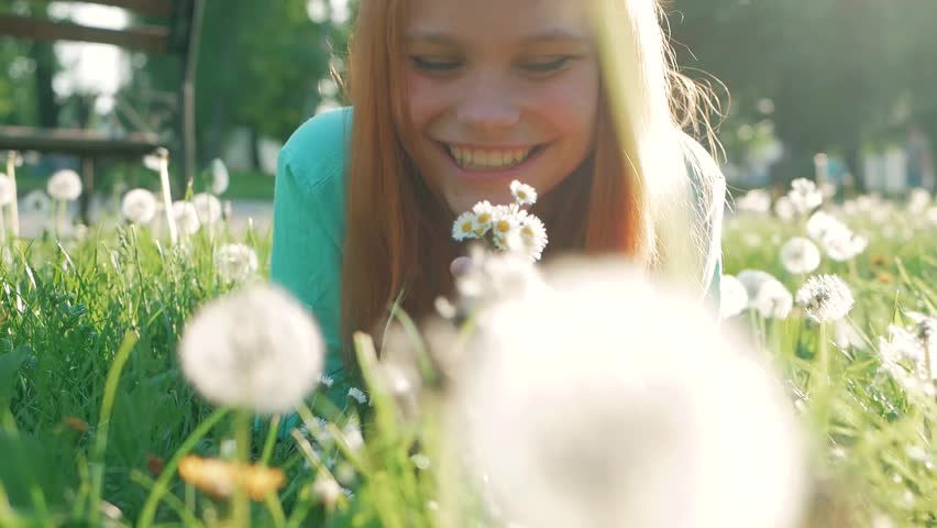 Beauty Girl lying on dandelions meadow and smelling flowers. Beautiful Spring Young Woman with red hair Outdoors Enjoying Nature. Healthy Girl in Green Grass. Allergy free
