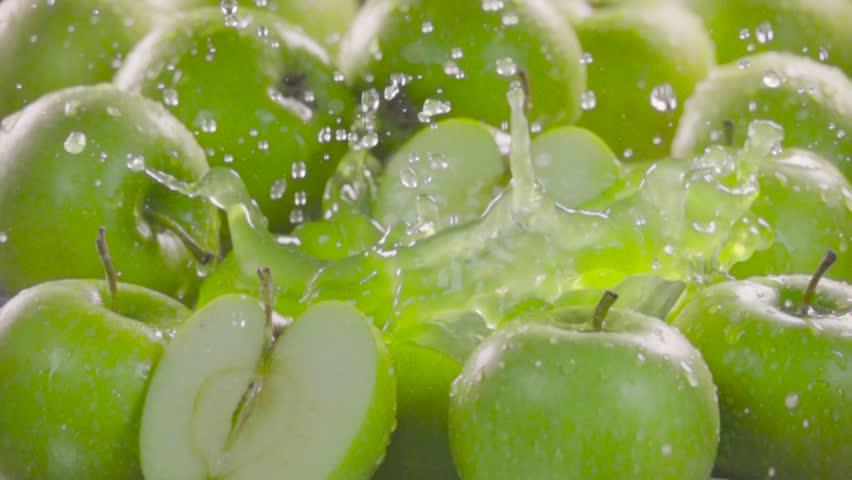 Green apple falling in juice with splash between apples. Slow motion 480 fps