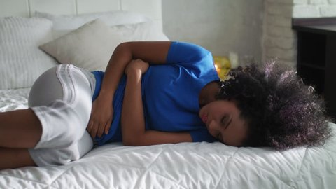 Sad young latina woman with menstrual pain. Black girl having cramps during period and lying on bed at home