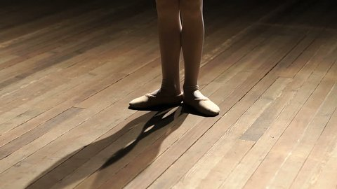 Close-up of a little girl's ballerina's feet on a wooden parquet floor on stage, slow motion. A little girl is studying ballet on stage in a choreographic school.