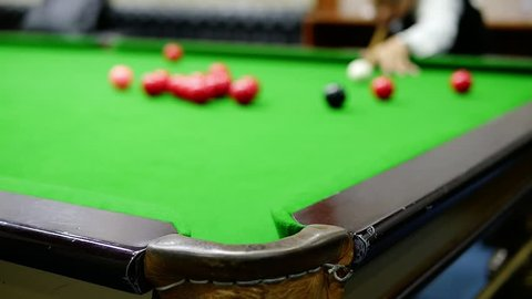 Slow motion of man playing snooker hit a target ball into the corner pocket - snooker sport closeup concept