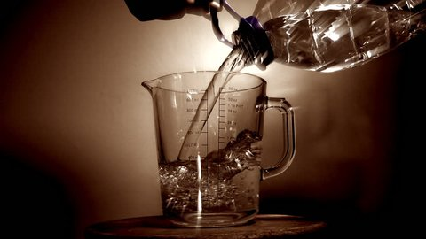 Slow motion shot of a man's hands holding a large plastic bottle and pouring water into a glass measuring jug.