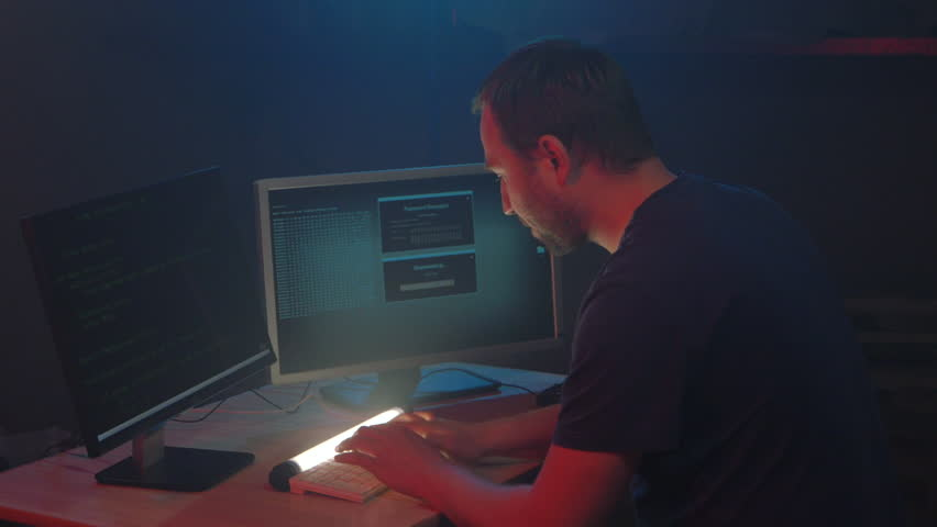 Cyber terrorist is hacking security system at night. Man is set on its work seriously. Male hacker smiles and shows the symbol fuck in the monitor display. cyber attack, internet, concept.