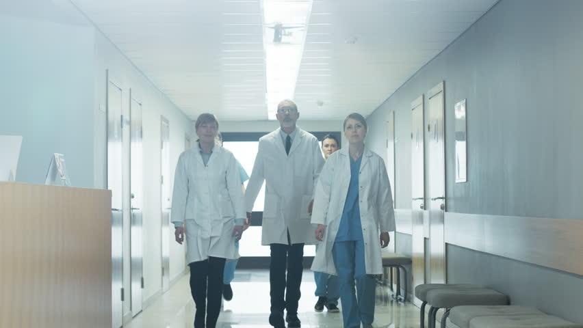 Team of Doctors, Nurses and Assistants Walking through the Hallway of the Hospital. Professional Medical Personnel Working, Saving Lives. Slow Motion. Shot on RED EPIC-W 8K Helium Cinema Camera.