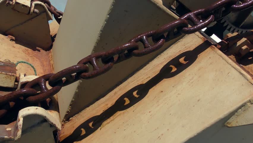 A moving anchor chain casts a shadow on the ship's part.