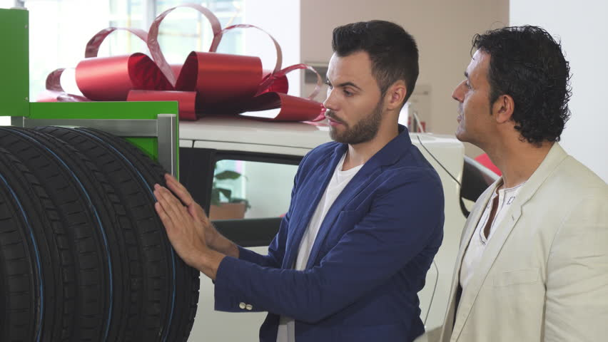 Young salesman helping his mature customer choosing car tires | Shutterstock HD Video #1011632795