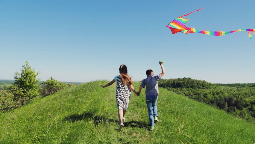 Rear view Children running to the top of a hill with flying kite in hand. Slow Motion. Sunny spring day | Shutterstock HD Video #1011671975