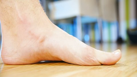 Flat feet forcing arch up exercise close-up 4K. Low angle view of person's foot in focus while lifting arch to make a healthy foot. Home dining room in the background out of focus.