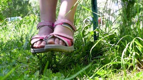 Baby feet in pink sandals close up swing on bench summer against green grass