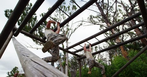 Military soldiers climbing monkey bars at boot camp