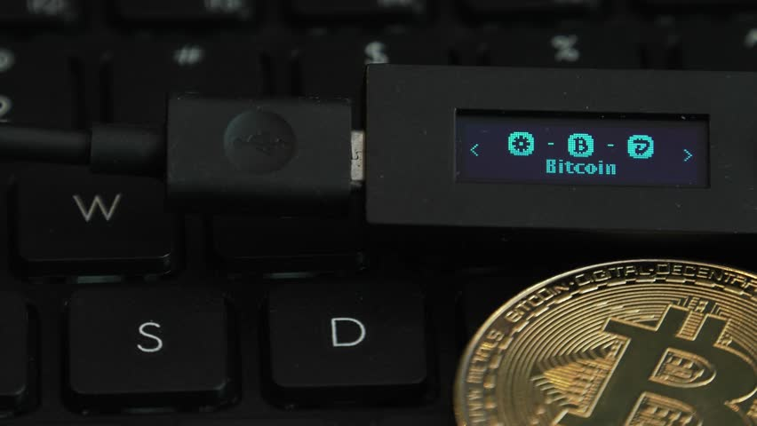 Cold hardware wallet for crypto. Connected to a computer to store Bitcoin, Litecoin and other cryptocurrencies. Notebook, Laptop keys in the background. BTC logo. Strobe effect on display.