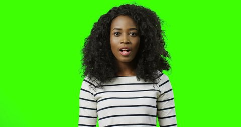 Young happy African American surprised woman in the striped blouse making wow face and being very cheerful in front of the camera. Green screen. Chroma key.