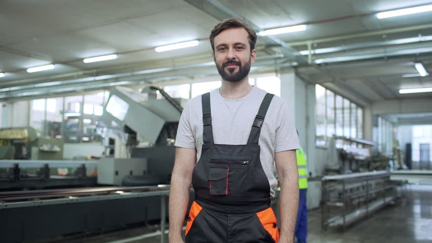 Portrait of adult employee man 30s wearing working overall standing with arms crossed during work in factory, slow motion