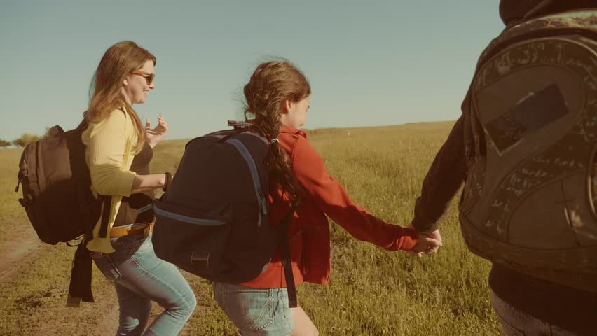 Happy family slow motion video walking on nature boy girl and mom in a field on trekking trip. tourists with lifestyle backpacks traveling. happy family travel tourism concept | Shutterstock HD Video #1011744575