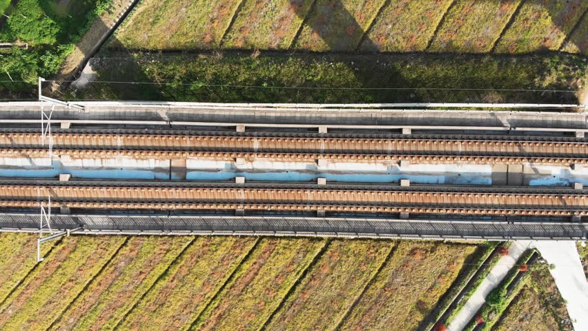 Looking down at Chinese high speed train tracks on raised platform. Drone shot of moving gaotie on elevated railway. | Shutterstock HD Video #1011757205