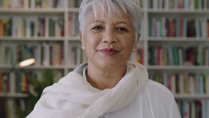 portrait of confident friendly indian middle aged teacher standing in library close up
