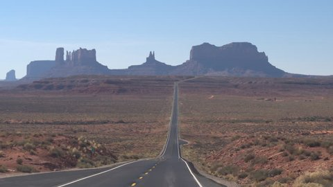 FIRST PERSON VIEW Driving along a straight empty road towards iconic Monument Valley landmark Utah USA. POV traveling on brand new highway road with yellow markings to Monument Valley desert landscape