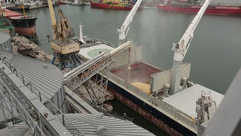 Panorama of ship loading grain crops on bulk freighter via trunk to open cargo holds at silo terminal in seaport. Cereals bulk transshipment to vessel. Transportation of agricultural products.