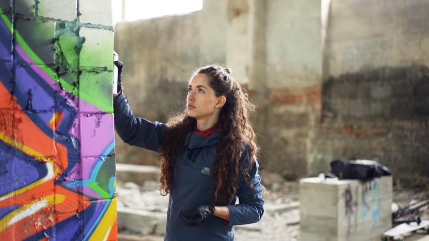 Slow motion of graffiti artist painting on wall in abandoned building using aerosol spray paint. Attractive girl with curly hair is busy with her work, she is looking at painting.