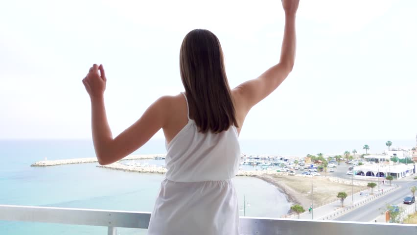 Funny young woman in white dress jumping with joy on terrace with sea view. Silly female raising arms up and dancing. Happy overjoyed girl having fun in slow motion
