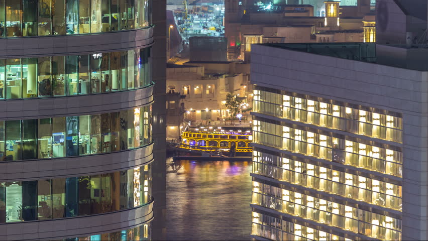 Windows of the multi-storey building of glass and steel lighting inside and moving people within timelapse. Aerial view of modern office skyscrapers in Dubai deira. Water of creek on background #1011839735