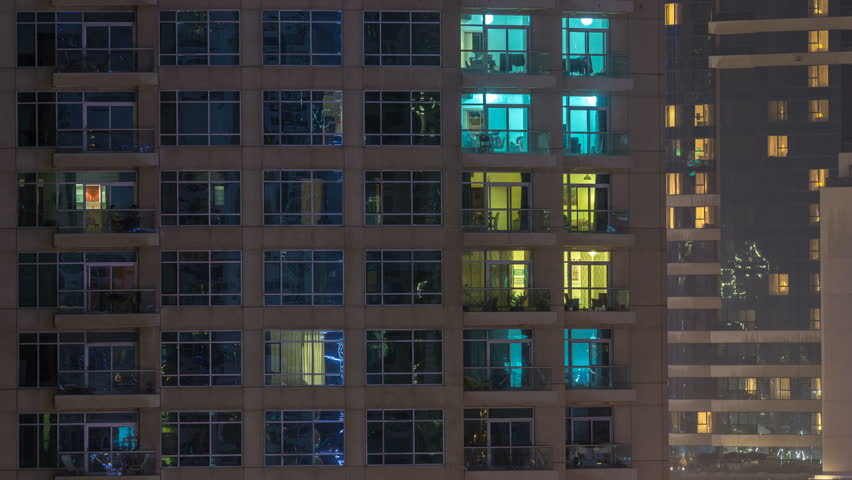 Windows of the multi-storey building of glass and steel lighting inside and moving people within timelapse. Aerial view of modern residential skyscrapers in Dubai marina. Pan up   Shutterstock HD Video #1011840515