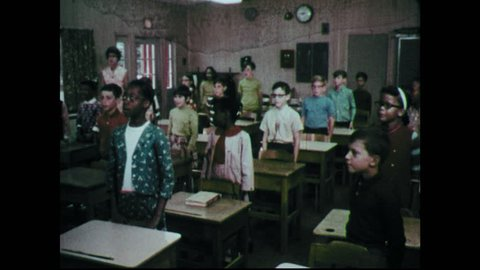 "1960s: Students stand at desks in classroom sing ""America"" anthem. Seal of the Department of Defense. Room of men holding up their hands making an oath."