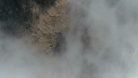 Aerial top down view of volcanic landscape first showing thick clouds then showing cooled down lava flows and in between the fertile soil with vegetation on landscape also showing road to Mount Etna