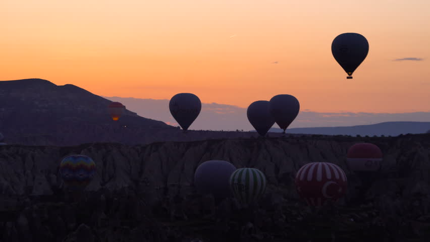 Silhouettes Lots of hot air balloons flying over valleys in Goreme, Turkey. Tourists from all over the world come to Cappadocia to make a trip in a hot-air balloons.