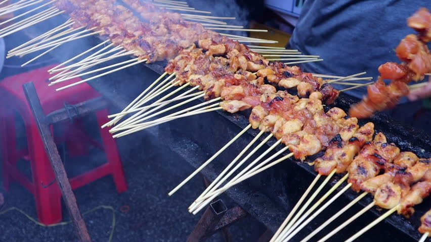 Vendor grilling smoking chicken satay over smoking charcoal at pasar market