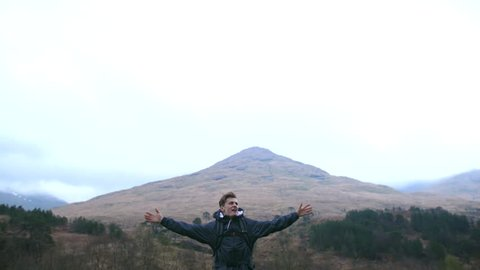 4K Young traveller dancing and looking at the view of a mountain in the Scottish Highlands. An ecstatic student back packing and nature trekking through rural landscape. A British tourist exploring