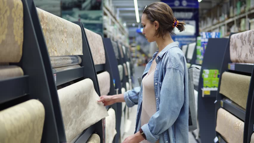 Shopping centre. Young female in casual clothes standing in department of goods for home, choosing wallpapers. Thinking to buy, unfolds the light one roll, example. Side view | Shutterstock HD Video #1011894305