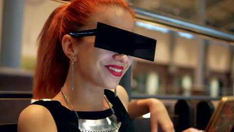 Stylish red hair posh woman watches mobile phone news and smiling in mall indoor close-up