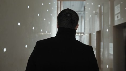 Back view of businessman walking in modern office building. Stock. The businessman stay in the business center