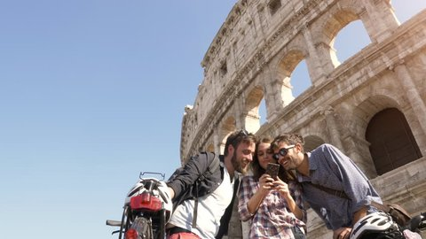 Three happy young friends tourists with bikes and backpacks at Colosseum in Rome using smartphones browsing selfies pictures on sunny day slow motion steadycam ground shot