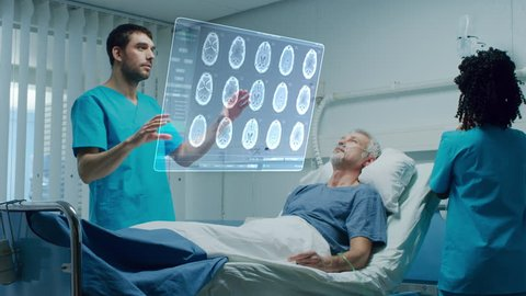 Futuristic Medical Ward with Sick Patient Lying in Bed and Doctor using Gestures and Augmented Reality Interface. Doctor Looks at Brain Scans and Medical History of the Patient. Shot on RED EPIC-W 8K.