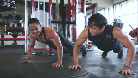 Sporty man push up giving high five to each other while working out together at gym