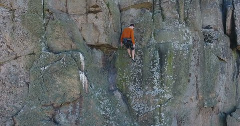 Aerial view. Climberman climbs on vertical rock. Smooth floating aerial footage of a rock climber climbing in Rock Canyon. Safety ropes. Deep canyon with river at bottom