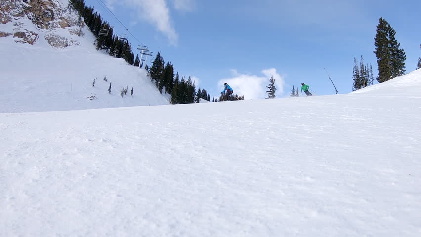 Two expert skiers, male and female make a dynamic turn in slow motion past wide-angle camera on a Utah ski slope.